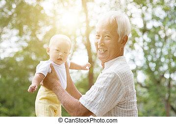 Grandparent and grandchild at park.