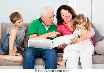 Grandparent And Grandchildren Looking At Photo Album