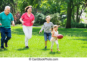 Grandparent And Grandchildren Playing With Rugby Ball