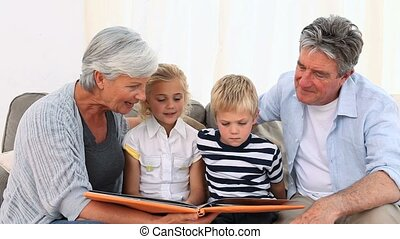 Grandparent showing theirs grandchilds a photo album