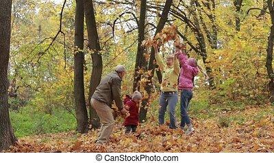 Grandparents and children with leaves in autumn