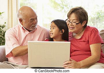 Grandparents And Grandaughter Using Laptop Computer At Home