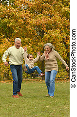 Grandparents and grandchild together in autumn park