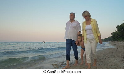 Grandparents and grandchild walking on the beach