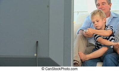 Grandparents and grandchild watching tv