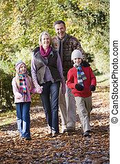 Grandparents and grandchildren on walk through autumn woods
