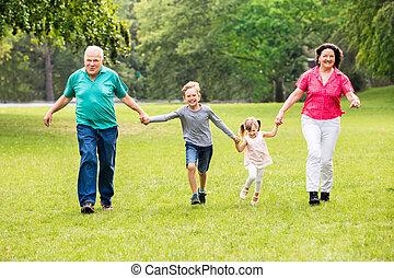 Grandparents And Grandchildren Running In Park