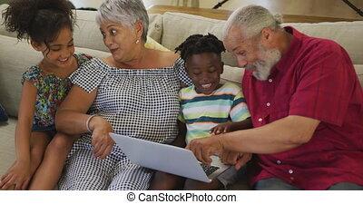 Grandparents and grandchildren using laptop at home - Senior...