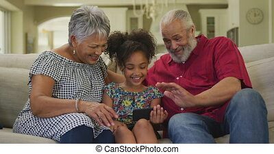 Grandparents and granddaughter using smartphone at home - ...