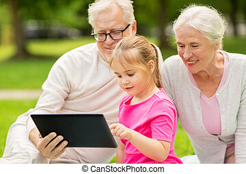 grandparents and granddaughter with tablet pc