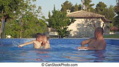Grandparents and grandson having fun in the pool