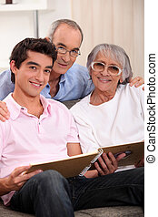Grandparents and grandson looking through family album