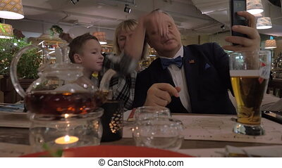 Grandparents and grandson making selfie during family dinner in restaurant