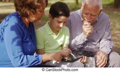 Grandparents And Grandson Studying Homework On Tablet PC