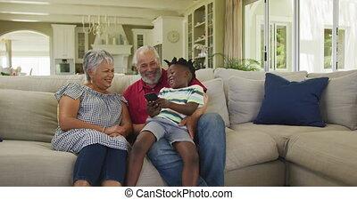 Grandparents and grandson using smartphone at home - Senior ...