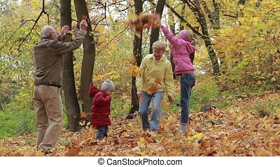 Grandparents and kids having fun in autumn park