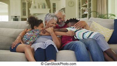 Grandparents embracing their grandchildren at home - Senior ...