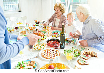 Grandparents Enjoying Family  Dinner in Sunlight