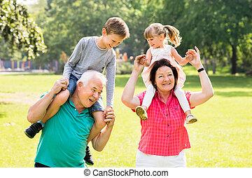 Grandparents Giving Grandchildren Piggyback Ride - Happy...