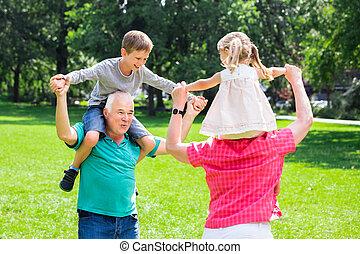Grandparents Giving Grandchildren Piggyback Ride In Park -...
