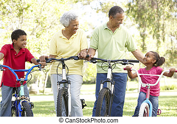 Grandparents In Park With Grandchildren Riding Bikes