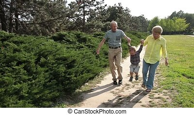 Grandparents lifting up toddler boy outdoor