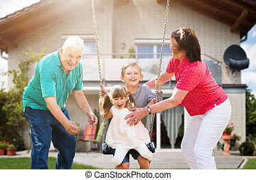 Grandparents Looking At Their Grandchildren Playing On Swing