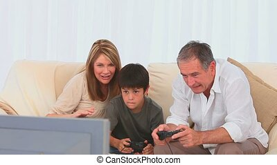 Grandparents playing video games with their grandson