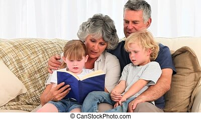 Grandparents reading a book to thei