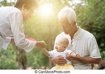 Grandparents taking care grandson outdoors.