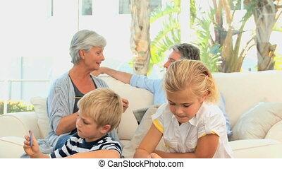 Grandparents talking while grandchild are makgin puzzle