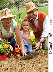 Grandparents teaching little girl the ways of gardening - planting flowers together