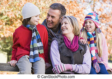 Grandparents with grandchildren outdoors in park smiling (selective focus)