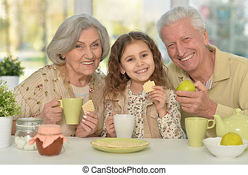 grandparents with granddaughter drinking tea at home