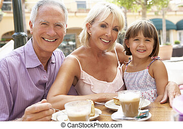 Grandparents With Granddaughter Enjoying Coffee And Cake In ...