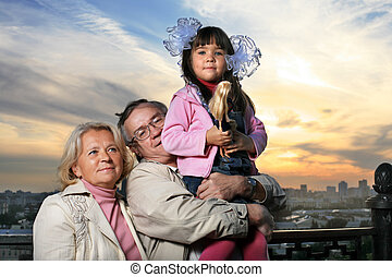 Grandparents with granddaughter outdoors at sunset