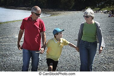 Grandparents with grandson walking at the beach