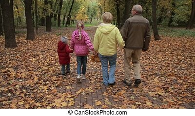 Grandparents with kids walking along autumn path