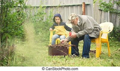 Grandson and grandfather sitting by the fire in the yard