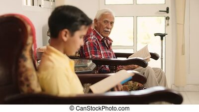 Grandson And Grandpa Reading Book And Relaxing At Home -...