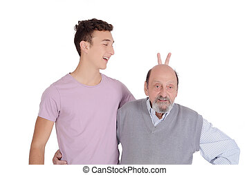 Grandson joking his grandfather with bunny ears