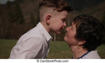 Grandson kisses grandmother on cheek. Relationships between generations, family