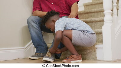 Grandson tying grandfather shoe laces at home - Senior ...