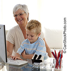 Grandson using a computer with his grandmother