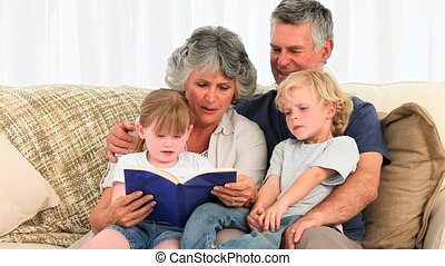 Grandsparents reading a book to their grandchildren
