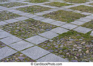 Granite cobblestoned pavement background. Full frame of regular square cobbles in rows.