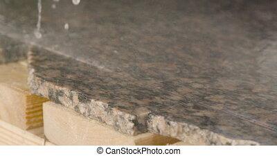 Granite processing in manufacturing. Cutting granite slab...