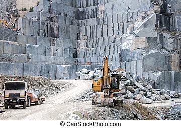 Granite quarry - Buldozer and truck in a granite quarry on...