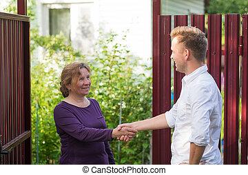 grannar, stående, kvinna, fence., ung, äldre, talande, diskutera, nyheterna, man