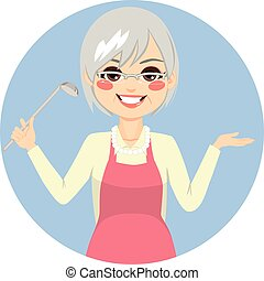 Happy granny cooking with apron holding kitchen spoon